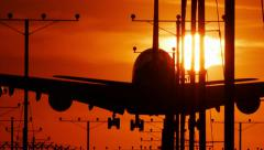 Jumbo jet plane landing in airport at sunset. Slow motion. - stock footage