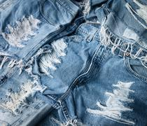 Heap of torn and frayed, threadbare jeans Stock Photos