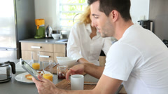 young couple using digital tablet at breakfast time - stock footage