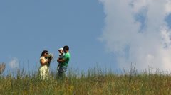 Beautiful mother, father holding baby in arms standing on blossom ridge hill Stock Footage