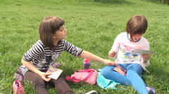 Two Beautiful Little Girls Sitting On Green Grass And Talking To Each Other - stock footage