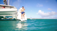 Man diving from catamaran deck into the sea Stock Footage