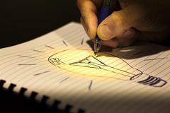 Stock Illustration of concept of idea: writing a light bulb in a copybook
