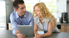 young couple websurfing with tablet in home kitchen - stock footage