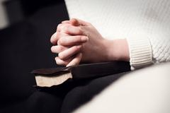 Praying woman folding hands over bible Stock Photos