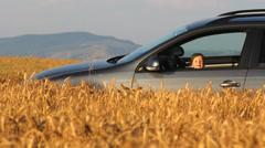 Funny little baby on the car wheel have fun, countryside road, grain crop Stock Footage