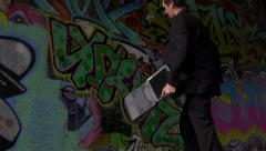 Business Man Destroys his Notebook Computer against Graffiti Wall Stock Footage