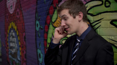 Young business man gets great news in front of a graffiti covered wall Stock Footage