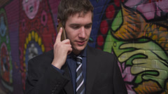 Young Business Man on Smart Phone in Front of Graffiti Wall Stock Footage