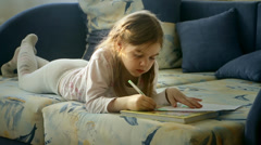 Little girl paints and watches TV Stock Footage
