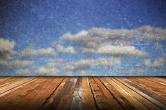 abstract scratched backdrop with wood terrace and grungy beautiful blue sky - stock illustration