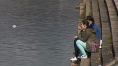 People sit on the stairs next to the river, on the banks of the river Stock Footage