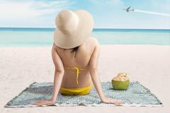 Sexy girl on beach looking at airplane Stock Photos
