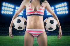 Sexy woman holding soccer balls at field Stock Photos