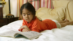 Cute little girl looking at her coloring book in bed Stock Footage