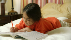 Cute little girl coloring while laying in bed Stock Footage