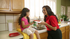 Wide shot mom gives dish to young daughter to dry Stock Footage