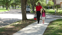 Mom walking her young daughter home from school Stock Footage