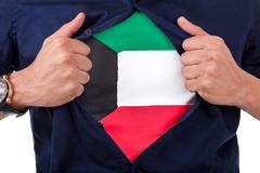 Young sport fan opening his shirt and showing the flag his country kuwait, ku Stock Photos