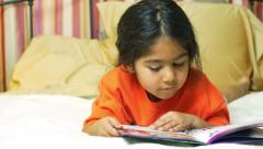 crane up to little girl reading in bed 4k - stock footage