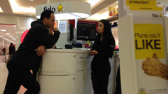 People asking fido sales clerk about cellphone plan - stock footage