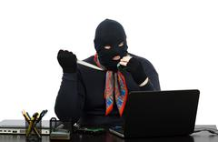 robber in balaclava with knife talking on the cell phone - stock photo