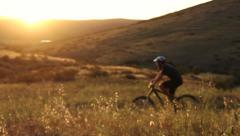 Man Mountain Bike Riding In Meadow At Sunset Stock Footage