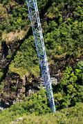 workers climing supporting pole, sky bridge, langkawi island - stock photo