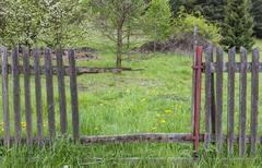 gap in an old crumbling wooden fence - stock photo