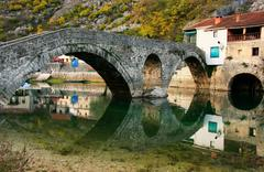 arched bridge reflected in crnojevica river, montenegro - stock photo