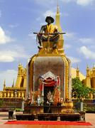 statue in front of pha that luang temple complex, vientiane, laos - stock photo