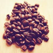 coffee beans on wooden background with retro filter effect - stock photo