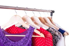 Dresses of different colors on wooden hangers Stock Photos