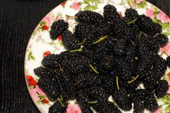 Ripe black mulberry in a plate Stock Photos