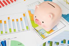 Stock Photo of piggy bank with business charts