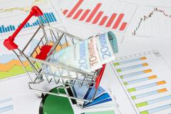 Stock Photo of market cart over business charts