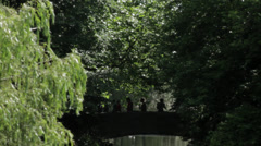 People walking through Old bridge in a park Stock Footage