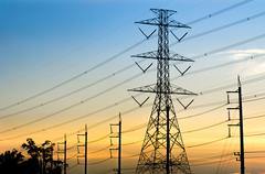 High-voltage electrical transmission towers with sunset background. Stock Photos