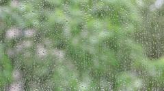 Raindrops on window glass, dripping, heavy rain, green tone, weather, background Stock Footage
