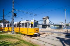 yellow tram on the river bank of danube in budapest - stock photo