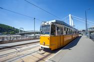 Stock Photo of yellow tram on the river bank of danube in budapest