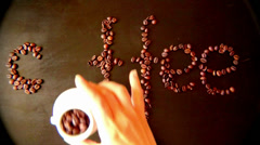 The inscription COFFEE made by women on the table from coffee beans Robusta Stock Footage