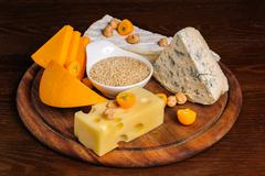 various cheeses with nuts and fruits on wooden plate - stock photo