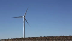 Windmill spinning in front of blue sky Stock Footage