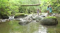 Mixed race girls walking up creek bed, Bellingham, Washington, United States Stock Footage
