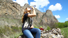 Young girl drinks pure water from a bottle on the background of mountains Stock Footage