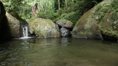 Mixed race girls jumping off rock into creek and swimming, Bellingham, Stock Footage