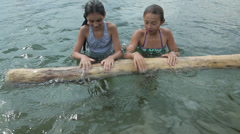 Mixed race girls swimming in lake and playing with log, Bellingham, Washington, Stock Footage
