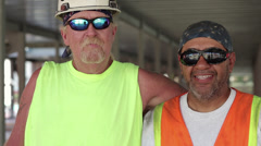 Construction workers standing together wearing sunglasses Stock Footage