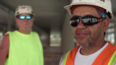 Construction workers wearing sunglasses with one worker in foreground Stock Footage